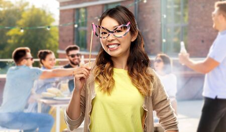 asian woman with big party glasses over rooftop Banco de Imagens