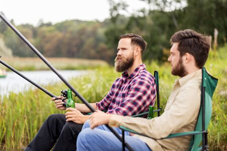 male friends fishing and drinking beer on lake Stock Photo