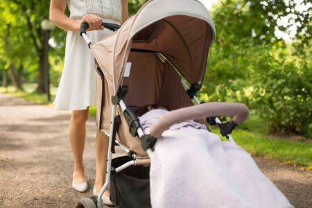 mother with child in stroller walking at park Stock Photo - 127780695