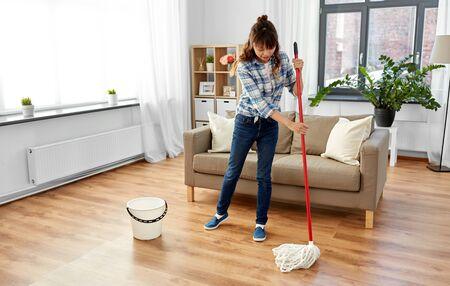 Frau oder Hausfrau mit Moppreinigungsboden zu Hause Standard-Bild