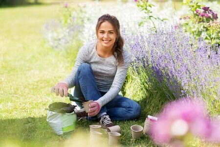 gardening and people concept - happy young woman filling pots with soil at summer garden