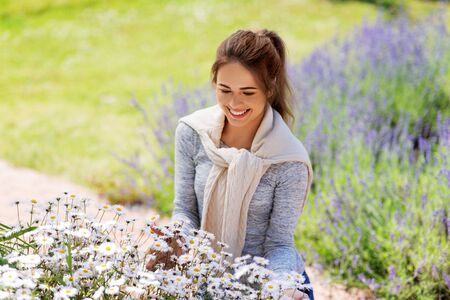 gardening and people concept - happy young woman with chamomile flowers at summer garden