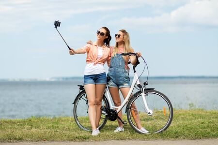 teenage girls with bicycle taking selfie in summer