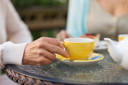 hand of senior woman drinking tea at outdoor cafe Stock Photo