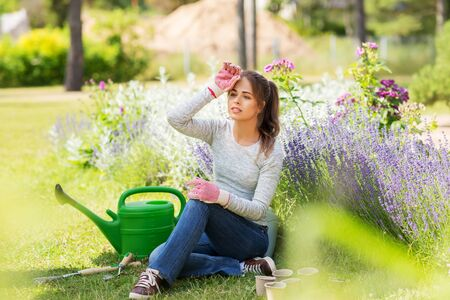 tired young woman with garden tools in summer