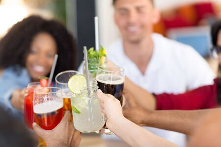 friends clinking glasses at bar or restaurant