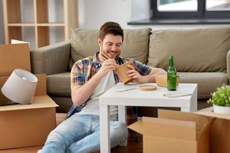 smiling man eating takeaway food at new home Stock Photo