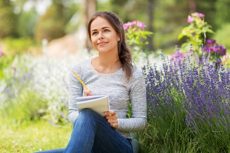 young woman writing to notebook at summer garden