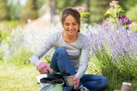 woman filling pots with soil at summer garden Banque d'images - 127878717