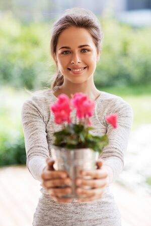 young woman with cyclamen flowers at summer garden Stock Photo