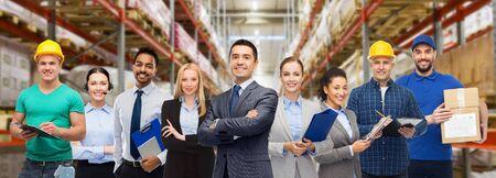 Negocio logístico, servicio de entrega y concepto de personas - feliz equipo internacional de empleados sobre fondo de almacén