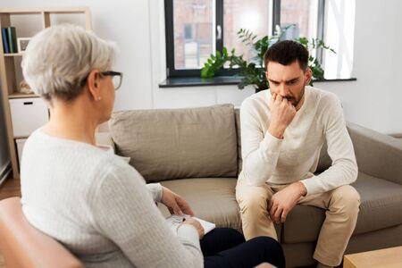 senior woman psychologist and sad man patient Stock Photo