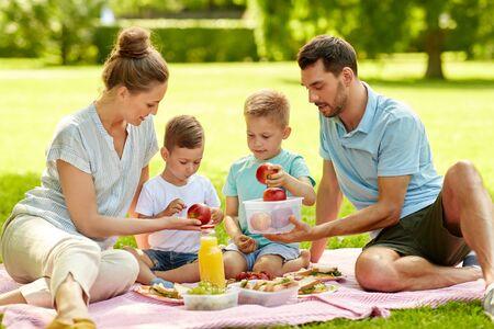 famille heureuse ayant pique-nique au parc d'été