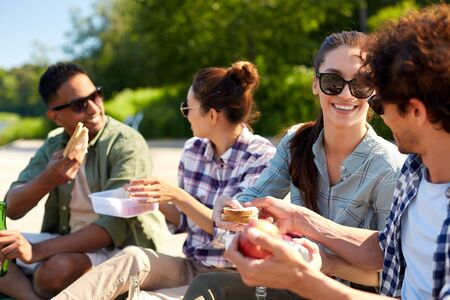 Amigos felices haciendo un picnic en el muelle del lago en verano Foto de archivo