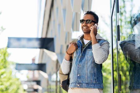 man with backpack calling on smartphone in city Zdjęcie Seryjne