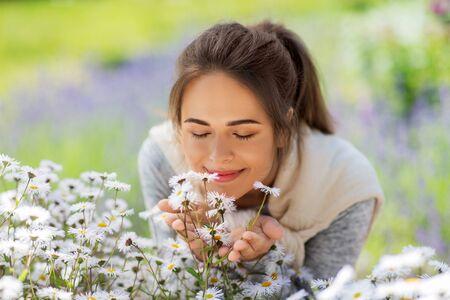 Cerca de mujer oliendo flores de manzanilla