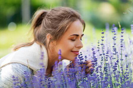 young woman smelling lavender flowers in garden
