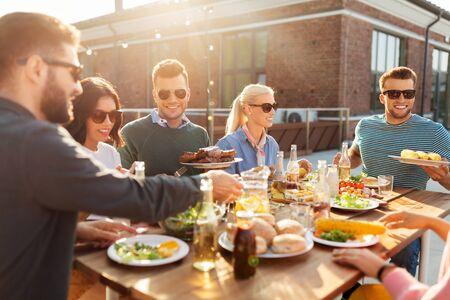 glückliche Freunde, die bei der Grillparty auf dem Dach essen Standard-Bild