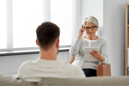 senior woman psychologist and young man patient Imagens