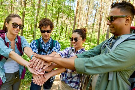 friends with backpacks stacking hands in forest