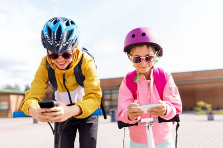 school children with smartphones and scooters