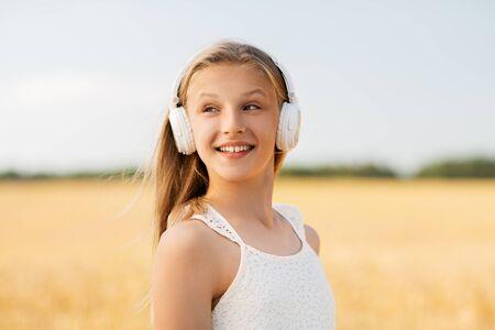 happy girl in headphones on cereal field in summer
