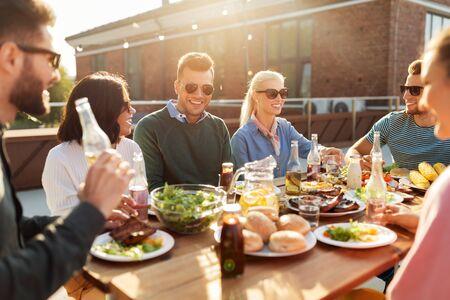 Freunde beim Abendessen oder Grillparty auf dem Dach Standard-Bild