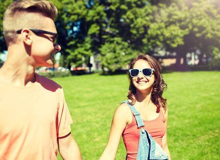 happy teenage couple walking at summer park Stockfoto