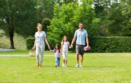 Familia con canasta de picnic caminando en el parque de verano