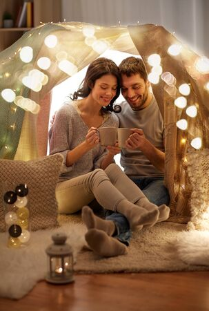 couple drinking coffee or tea in kids tent at home