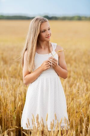girl with spikelet of wheat on cereal field
