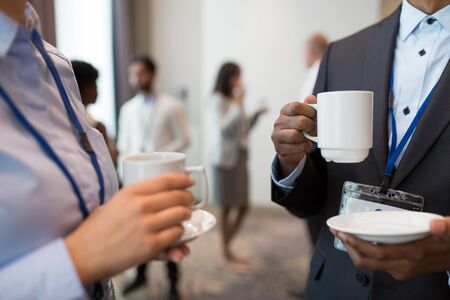business, communication and education concept - international group of people with conference badges drinking coffee and talking at brake