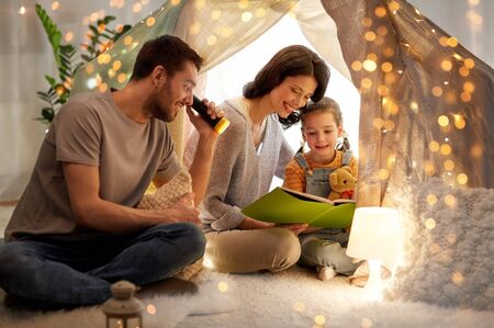 happy family reading book in kids tent at home Imagens