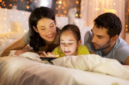 family with tablet pc in bed at night at home Imagens