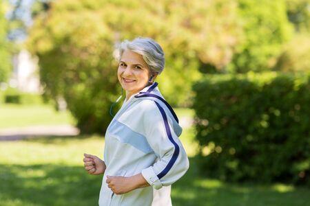 senior woman with earphones running in summer park 版權商用圖片