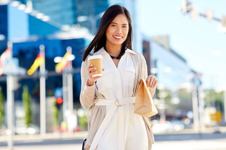 happy woman with takeaway coffee and lunch in city