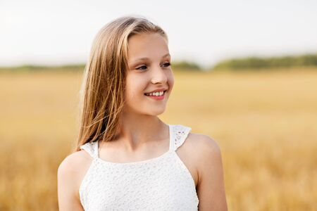smiling young girl on cereal field in summer