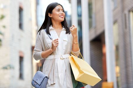 asian woman with shopping bags walking in city Stock Photo