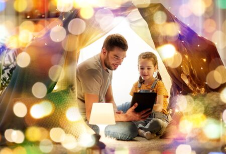 family with tablet pc in kids tent at home Imagens