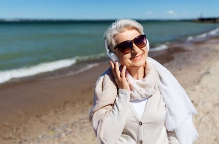 old woman in headphones listens to music on beach Imagens
