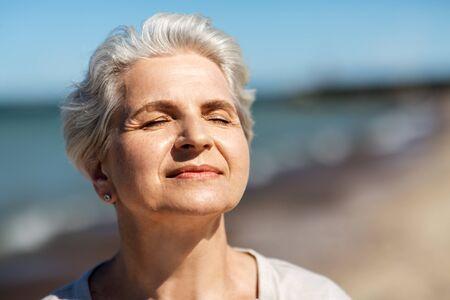 portret van een oudere vrouw die van de zon geniet op het strand