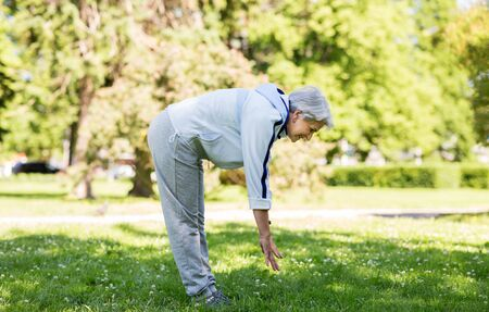happy senior woman exercising at summer park Imagens