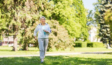 senior woman running along summer park Imagens