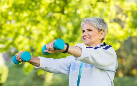 senior woman with dumbbells exercising at park