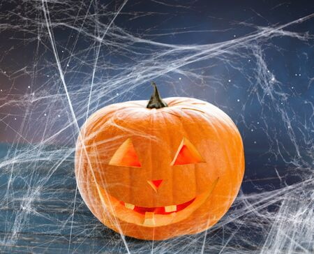holidays, halloween and decoration concept - pumpkin or jack o lantern on table and spiderweb over starry night sky background