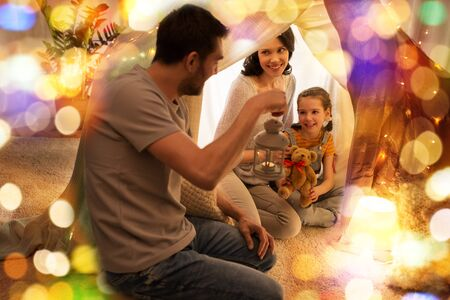 happy family playing in kids tent at night at home