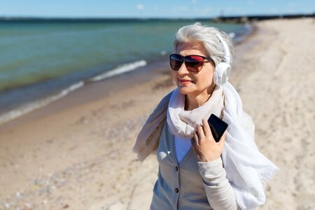 old woman in headphones with smartphone on beach