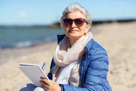 senior woman writing to notebook on summer beach Imagens
