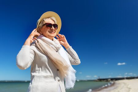 happy senior woman in sunglasses and hat on beach Imagens