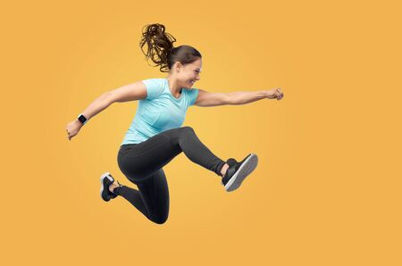 happy fit young woman jumping in air Banque d'images - 128861122